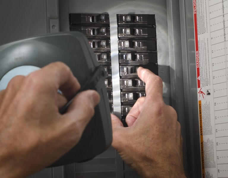 man throwing circuit breaker at residential electrical panel