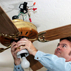 electrician in Laurel installing a ceiling fan
